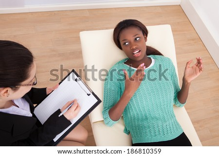 High angle view of female patient conversing with psychologist in clinic - stock photo
