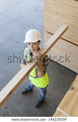 High angle view of female worker carrying wooden plank on shoulder - stock photo