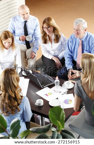 High angle view of financial business people sitting at meeting. Businesswomen and businessmen sitting at desk in front of computer and consulting from financial investment. Teamwork at office.