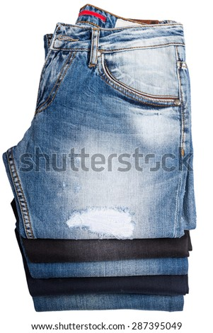 High Angle View of Folded and Stacked Blue Jeans - Looking Down at Denim Pants in Varying Color Washes and Styles in Neat Stack on White Background - stock photo