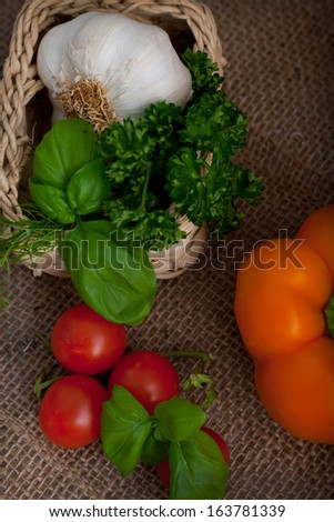 High angle view of fresh cooking ingredients including basil, tomatoes, bell pepper, parsley and a whole garlic bulb in a wicker basket over a hessian background - stock photo