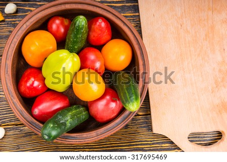 High Angle View of Fresh Picked Vegetables in Bowl Beside Wooden Cutting Board on Rustic Wooden Table with Wood Grain - stock photo