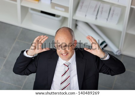 High angle view of frustrated mature businessman raising arms in office - stock photo