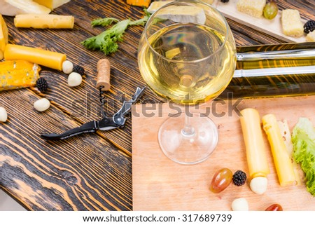 High Angle View of Glass of White Wine on Rustic Wooden Table Surrounded by Cheeses and Fruit for Gourmet Cheese Board - stock photo