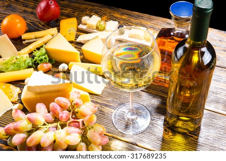 High Angle View of Glass of White Wine on Rustic Wooden Table with Bottles, Variety of Cheeses and Fresh Fruits - stock photo
