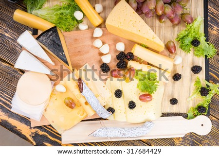High Angle View of Gourmet Cheese Board Featuring Variety of Cheeses, Cured Meat and Garnished with Fresh Fruit, Served on Rustic Wooden Table - stock photo