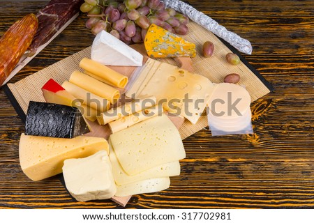 High Angle View of Gourmet Cheese Board Featuring Wide Variety of Cheeses and Garnished with Fruit, Served on Rustic Wooden Table with Copy Space