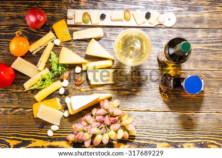 High Angle View of Gourmet Cheeses, Fruit and White Wine on Rustic Wooden Table with Copy Space - stock photo