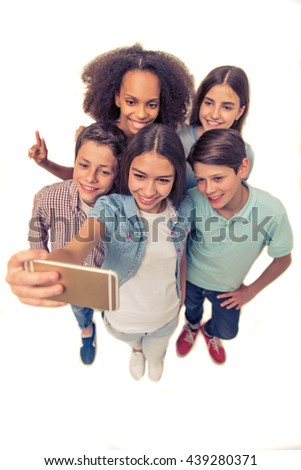 High angle view of group of teenage boys and girls making selfie using a smartphone and smiling, isolated on white - stock photo