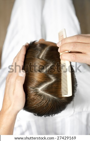 high angle view of hairdresser using comb - stock photo