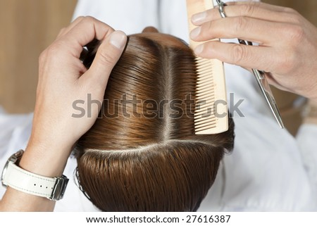 high angle view of hairdresser using comb