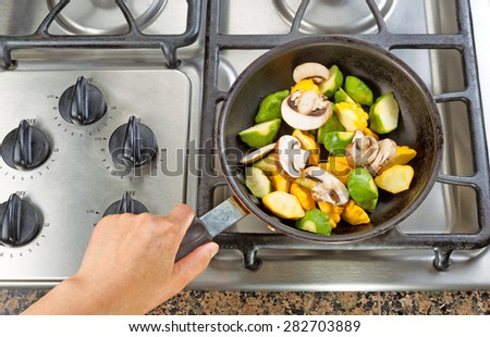 High angle view of hand holding frying pan while cooking vegetable in pan on top of stove. - stock photo