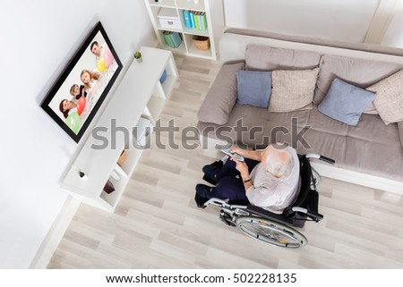 High Angle View Of Handicapped Grandmother Watching Movie On Television At Home