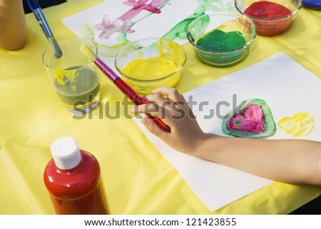 High angle view of hands holding paint brush in art class - stock photo