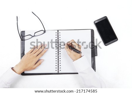 High angle view of hands writing on personal agenda to make a plan - stock photo