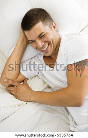 High angle view of handsome Caucasian mid adult man lying in bed smiling. - stock photo