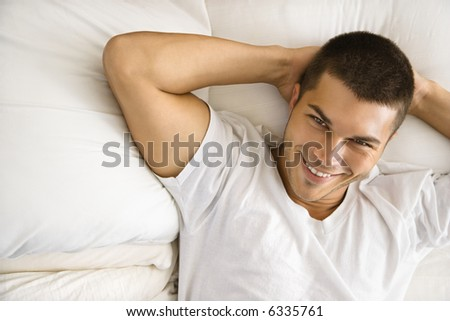 High angle view of handsome Caucasian mid adult man lying with hands behind head  smiling. - stock photo