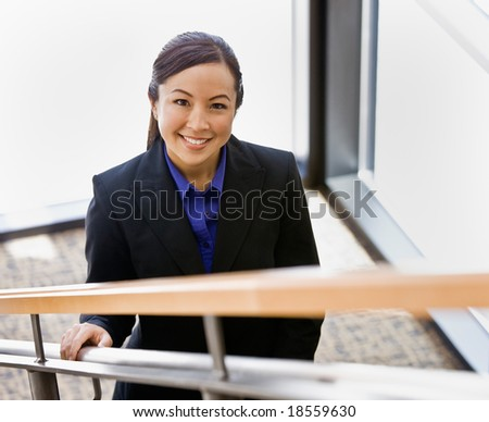 High angle view of happy Asian businesswoman ascending stairs - stock photo