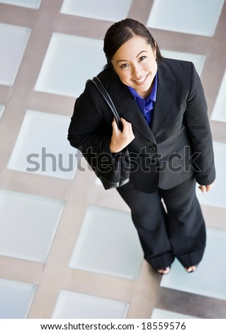 High angle view of happy businesswoman in full suit standing with purse - stock photo