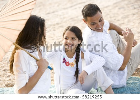 High angle view of happy Hispanic family with 9 year old daughter on beach - stock photo