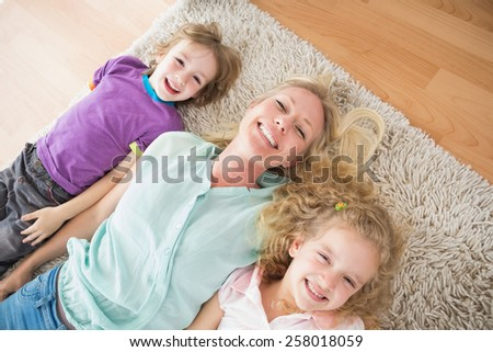 High angle view of happy mother and children lying on rug at home - stock photo
