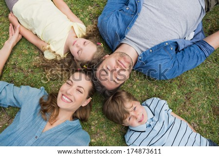 High angle view of happy parents and kids lying at the park - stock photo