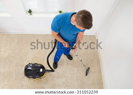 High Angle View Of Happy Worker Vacuuming Carpet - stock photo