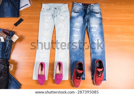 High Angle View of His and Hers Distressed and Torn Blue Jeans Laid Out Flat on Wooden Surface with Coordinating Shoes - Stylish Pink Loafers and Red Sneakers