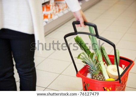 High angle view of human hand carrying red basket filled with fruits and vegetables - stock photo