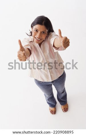 High angle view of Indian woman giving thumbs up - stock photo