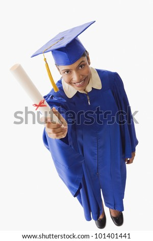 High angle view of Indian woman in graduation cap and gown holding diploma