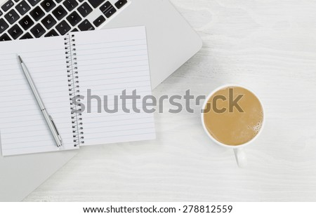 High angle view of laptop, coffee and blank notepad with silver pen on rustic white desktop. 