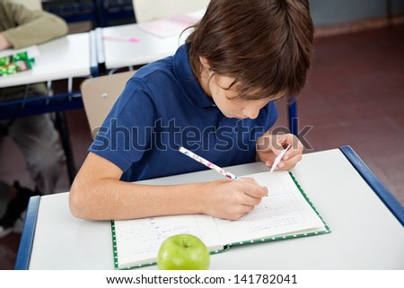 High angle view of little boy copying from cheat sheet at desk during examination - stock photo