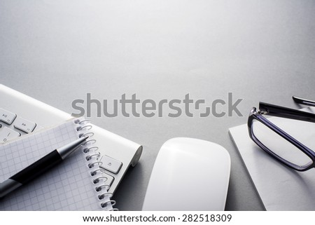 High Angle View of Mac Computer Keyboard and Mouse on Grey Desk with Note Book, Eyeglasses and Pen and Ample Copy Space - stock photo