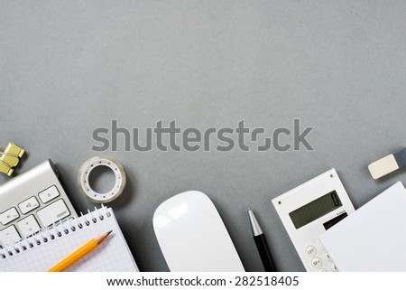 High Angle View of Mac Computer Keyboard and Mouse with Various Office Supplies Scattered on Grey Desk with Ample Copy Space - stock photo