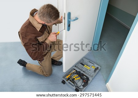 High Angle View Of Male Carpenter With Screwdriver Fixing Door Lock - stock photo