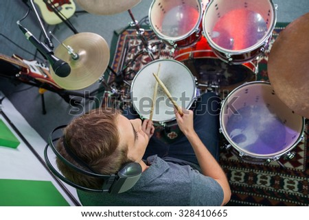 High angle view of male drummer performing in recording studio