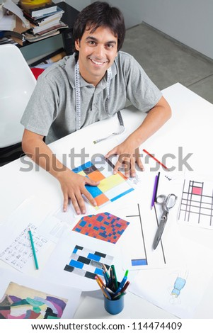 High angle view of male fashion designer sitting at table with outline designs and patterns at workshop - stock photo