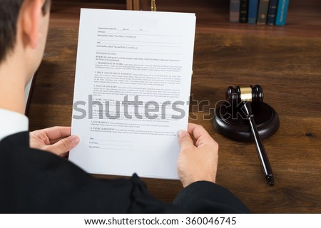 High angle view of male judge reading legal documents at desk in courtroom - stock photo