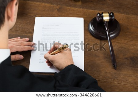 High angle view of male judge writing on legal documents at desk in courtroom - stock photo