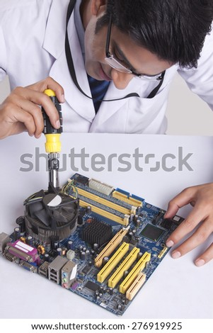 High angle view of male technician working on mother board at table