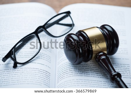 High angle view of mallet and eyeglasses on open legal book in courtroom - stock photo