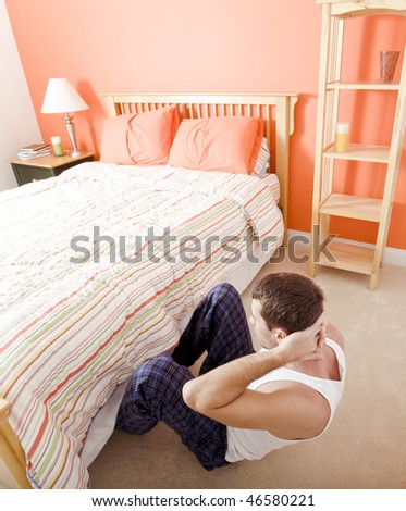 High angle view of man doing sit-ups in his bedroom, with his feet tucked under the bed frame. Vertical format. - stock photo