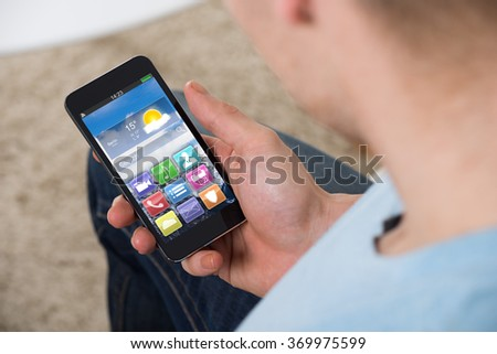 High angle view of man holding smartphone with colorful application icons at home - stock photo