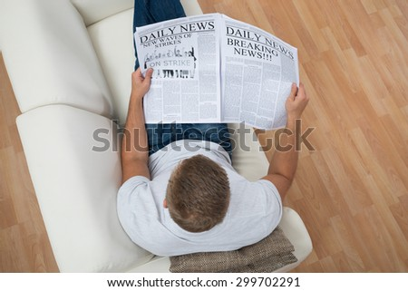 High Angle View Of Man Reading Newspaper On Sofa At Home