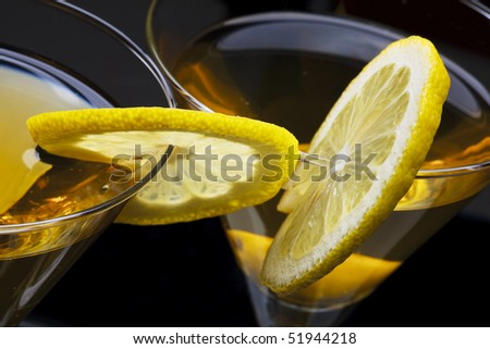 High angle view of martini with olives isolated on black focus on rim of glass and lemon slice. Shallow depth of field. - stock photo