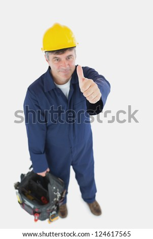 High angle view of mature man with tool bag showing thumbs up sign over white background - stock photo