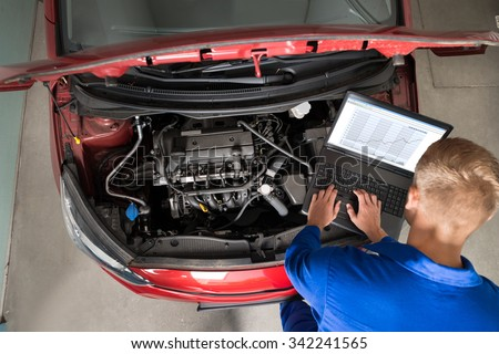 High Angle View Of Mechanic Examining Car Engine With Help Of Laptop - stock photo
