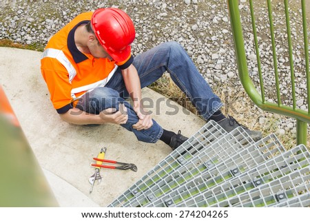 High angle view of mid adult worker suffering from leg pain by storage tank steps in park - stock photo