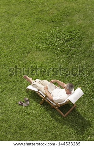 High angle view of middle aged man reading book on deck chair in garden - stock photo